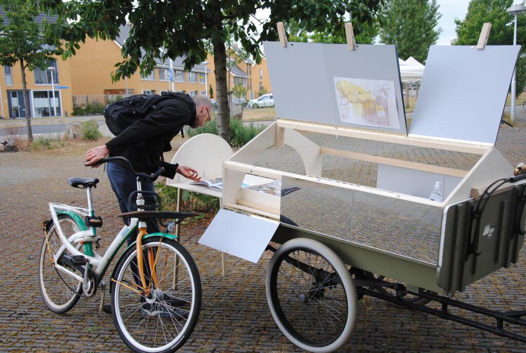 Image description: a person taking a peek into the cargo bike architecture's interior.