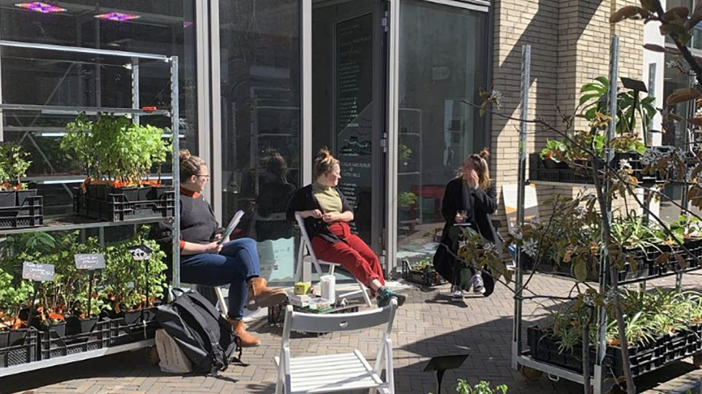 Image Description: Three people are sitting on chairs outside the depot in the Terwijde Winkelcentrum, they are surrounded by plants and pots that come from the plant farm Stekkers, and that can be bought directly from the depot.