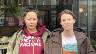 Image description: Ying Que, wearing a Zwarte Piet is Racisme sweater, and Staci Bu Shea, wearing a shirt saying Crip Resilience is Nature's Brilliance, standing next each other, while in front of the palm tree at the Stranded FM studio.